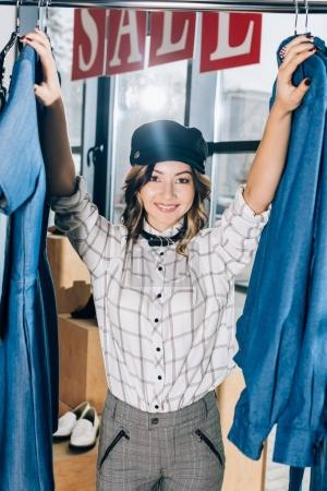 smiling young woman in clothing store on clearance day