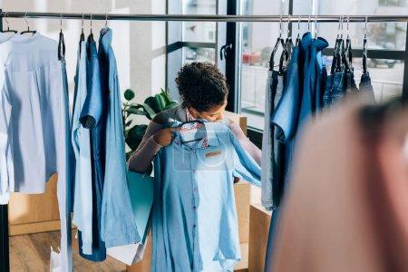 beautiful young woman looking at blue shirt at clothing store