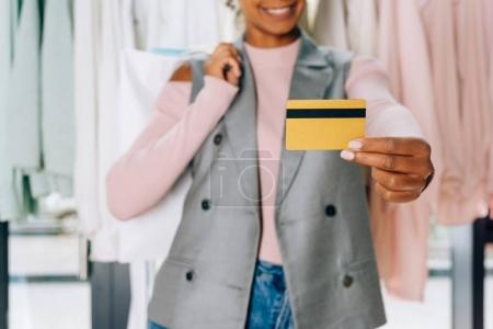 Photo for Beautiful young woman showing credit card at clothing store - Royalty Free Image