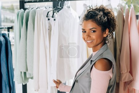 Photo for Young beautiful shopper looking for new clothes on hangers in store - Royalty Free Image