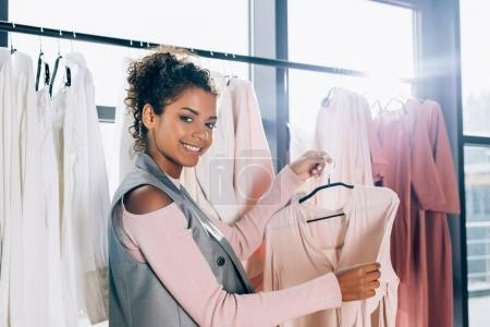 Photo for Happy beautiful shopper looking for new clothes on hangers in store - Royalty Free Image