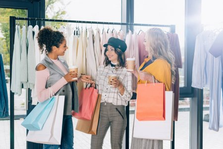 group of young women with shopping bags and coffee to go in clothing store