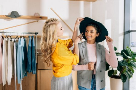 young stylish shopping buddies spending time in clothing store
