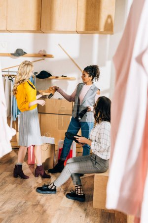 group of young women on shopping in shoes and clothing store