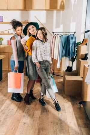 group of stylish young women taking selfie in clothing store