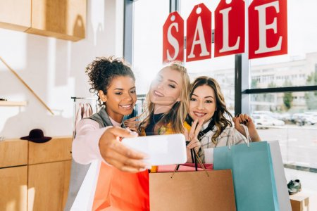 group of happy young women taking selfie on shopping