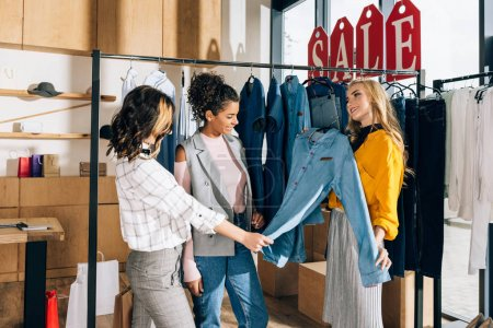Photo for Group of multiethnic shopaholics on shopping in clothing store - Royalty Free Image