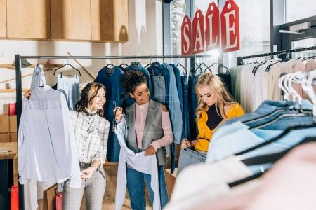 group of beautiful stylish women on shopping in clothing store