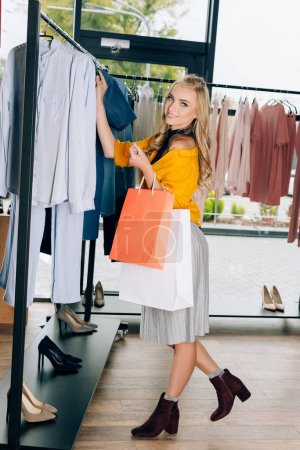 stylish young woman looking for new clothes on hangers in store