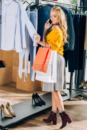 stylish young woman talking by phone and looking for new clothes in store