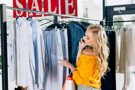beautiful young woman talking by phone and looking for new clothes in store