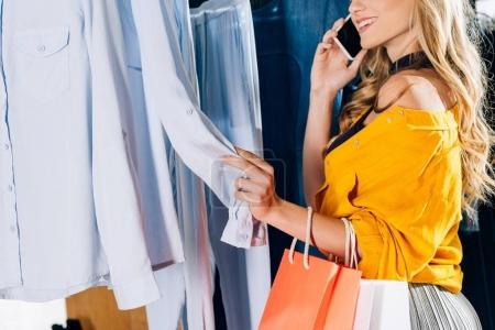 cropped shot of woman talking by phone and looking for new clothes in store
