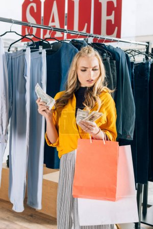 serious young woman counting cash in clothing store