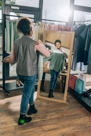 attractive young woman looking at mirror in clothing store