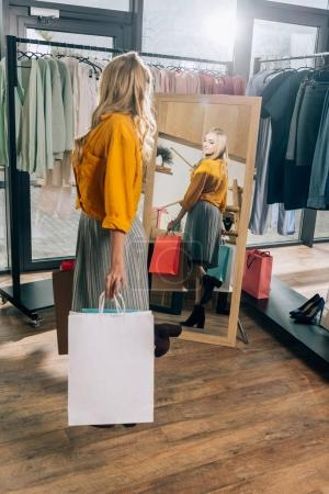 beautiful young woman looking at mirror in clothing store