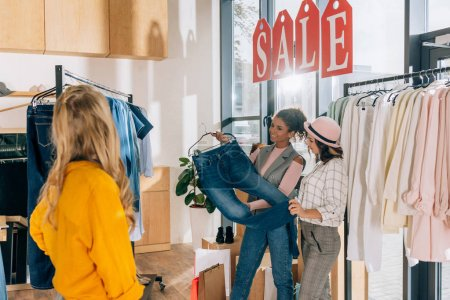 group of young shopaholics in clothing store on sale