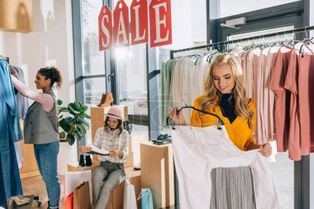 group of young women on shopping in clothing store on sale