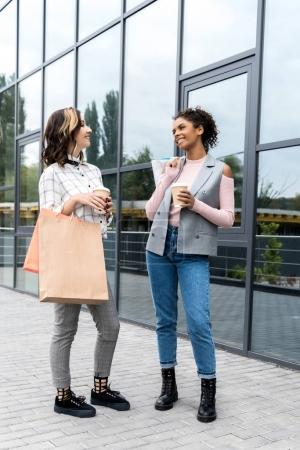 beautiful young women with shopping bags and coffee to go outdoors