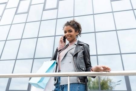 Photo for Bottom view of beautiful young woman with shopping bags talking by phone outdoors - Royalty Free Image