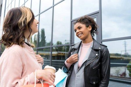 Photo pour Jeunes femmes élégantes avec des sacs à provisions et café pour aller parler à l'extérieur - image libre de droit