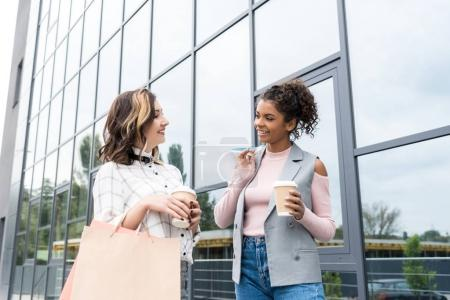 young stylish women with shopping bags and coffee to go talking outdoors