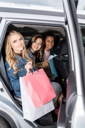 group of young women with shopping bags sitting in car