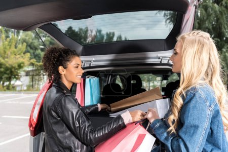 young stylish women packing shopping bags into car