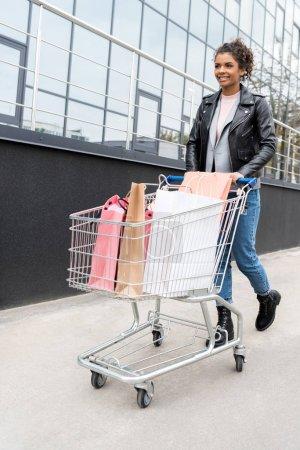 beautiful young woman walking with shopping cart outdoors