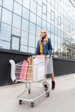 beautiful stylish woman on shopping with cart outdoors