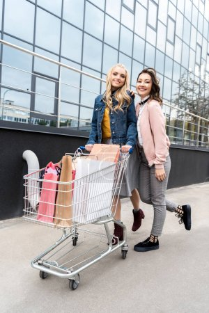 young stylish shopping buddies with cart of paper bags outdoors