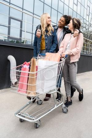 group of young women with shopping bags in cart riding outdoors near mall