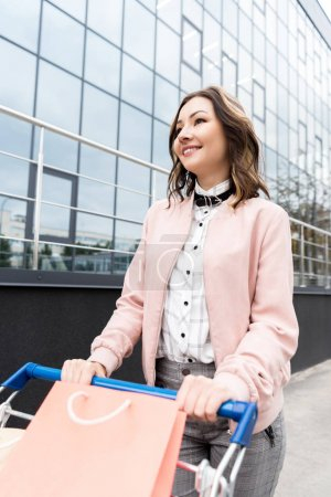 happy young woman on shopping with cart outdoors