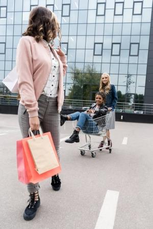 group of young women with shopping cart riding on parking