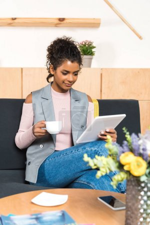 Photo for Beautiful young woman using tablet and drinking coffee in cafe - Royalty Free Image