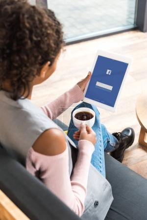 beautiful young woman using tablet with facebook on screen
