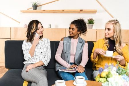 group of young girlfriends spending time together in cafe