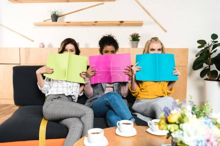 Photo for Group of young girlfriends covering faces with magazines in cafe - Royalty Free Image