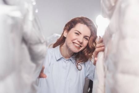 Foto de Sonriente trabajador mujer limpieza en seco mirando a cámara entre la ropa en bolsas de plástico colgando en el almacén - Imagen libre de derechos