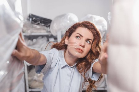female dry cleaning worker looking at clothing packed in plastic bags
