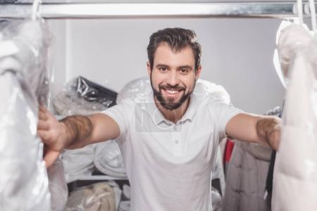 Photo for Dry cleaning worker at warehouse with clothing packed in plastic bags - Royalty Free Image