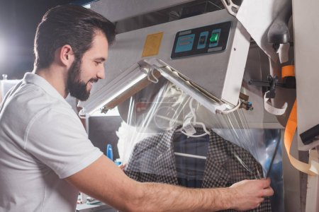 Photo for Dry cleaning worker packing jacket in plastic bag - Royalty Free Image