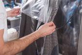 """Постер, картина, фотообои """"обрезанное выстрел Химчистка работника упаковки куртка в пластиковый пакет"""""""