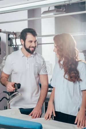 smiling young dry cleaning workers ironing clothes