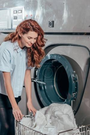 Photo for Happy female dry cleaning worker taking clothes out of washing machine - Royalty Free Image