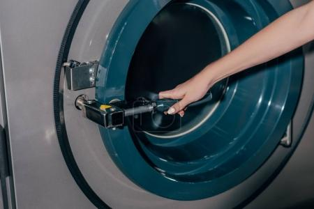 cropped shot of woman opening industrial washing machine