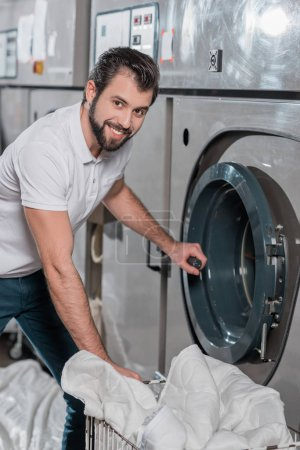 dry cleaning worker opening industrial washing machine