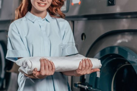 cropped shot of female dry cleaning worker holding stack of clean white clothes