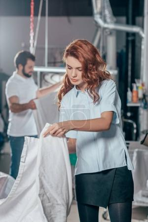 dry cleaning worker folding clean cloth at warehouse