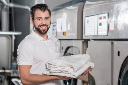 Photo for Happy dry cleaning worker holding stack of clean clothes - Royalty Free Image