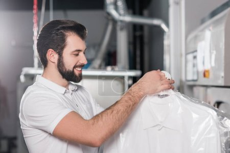 dry cleaning worker holding bags with clean clothing